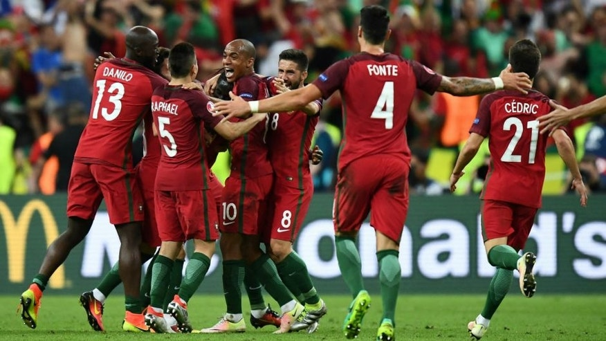 Portugal team players celebrate as they clinch the match 1-0 against France in the Euro 2016 final football match between France and Portugal at the Stade de France in Saint-Denis, north of Paris, on July 10, 2016. / AFP / FRANCK FIFE (Photo credit should read FRANCK FIFE/AFP/Getty Images)