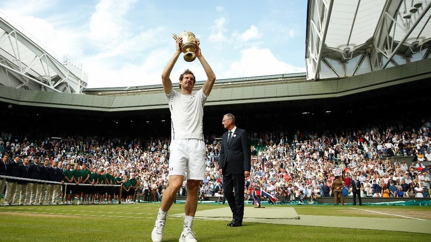 Andy Murray of Britain holds up his trophy after beating Milos Raonic of Canada in the men's singles final on day fourteen of the Wimbledon Tennis Championships in London, Sunday, July 10, 2016. (Andy Couldridge/Pool Photo via AP)