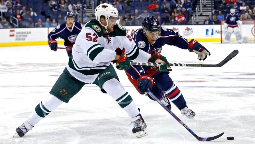 Minnesota Wild defenseman Zach Palmquist skates against Columbus Blue Jackets left wing Rene Bourque.