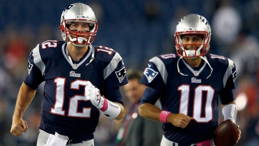 FOXBORO, MA - OCTOBER 05: Tom Brady #12 and Jimmy Garoppolo #10 of the New England Patriots warm up before a game against the Cincinnati Bengals at Gillette Stadium on October 5, 2014 in Foxboro, Massachusetts. (Photo by Jim Rogash/Getty Images)