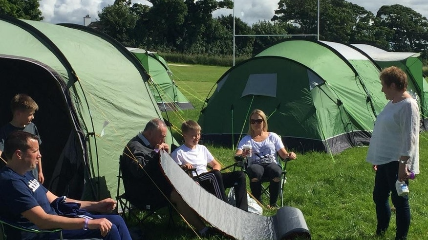 People sit outside their tent at the Marr Rugby Club in Troon, Scotland, Wednesday, July 13, 2016. For the first time, the R&A is giving a small group of fans the chance to camp out during the British Open, making things much more affordable for families and young adults. (AP Photo/Paul Newberry)