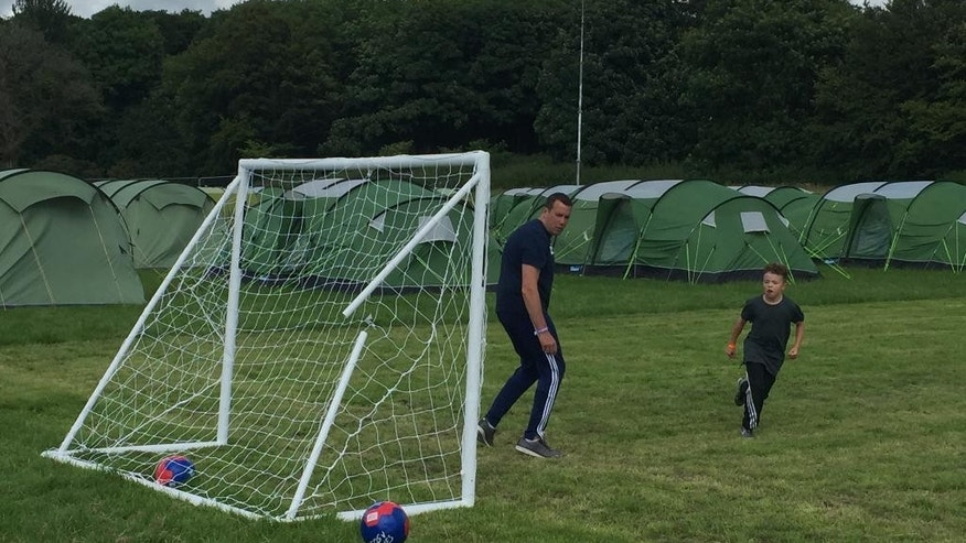 People who are camping at the Marr Rugby Club in Troon, Scotland, play a game of soccer, Wednesday, July 13, 2016. For the first time, the R&A is giving a small group of fans the chance to camp out during the British Open, making things much more affordable for families and young adults. (AP Photo/Paul Newberry)