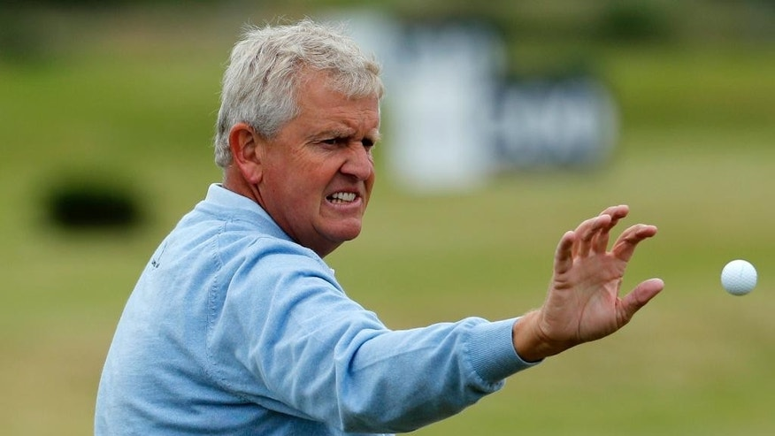 Colin Montgomerie of Scotland goes to catch a ball on the practice ground ahead of the British Open Golf Championship at the Royal Troon Golf Club in Troon, Scotland, Tuesday, July 12, 2016. The Open starts Thursday. (AP Photo/Ben Curtis)