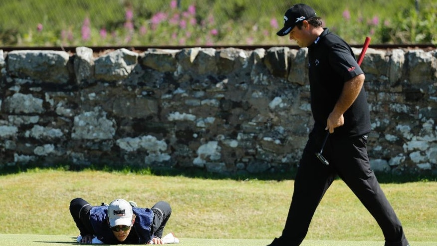 Patrick Reed's caddie Kessler Karain lies on the grounds as he helps line up the putt on the 11th green of the USduring the first round of the British Open Golf Championship at the Royal Troon Golf Club in Troon, Scotland, Thursday, July 14, 2016. (AP Photo/Ben Curtis)