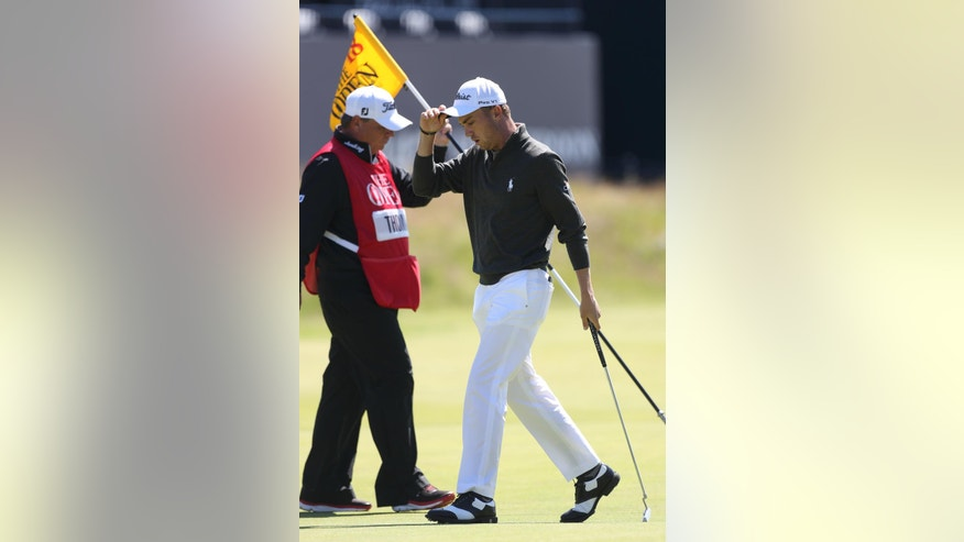 Justin Thomas of the United States lifts his cap as he walks off the 18th green after completing his the first round of the British Open Golf Championship at the Royal Troon Golf Club in Troon, Scotland, Thursday, July 14, 2016. (AP Photo/Peter Morrison)