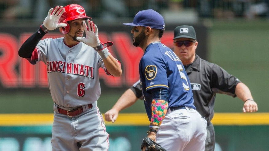 Cincinnati Reds' Billy Hamilton, left, calls for time after hitting a leadoff double off Milwaukee Brewers' Jimmy Nelson during the first inning of a baseball game Sunday, May 29, 2016, in Milwaukee. (AP Photo/Tom Lynn)