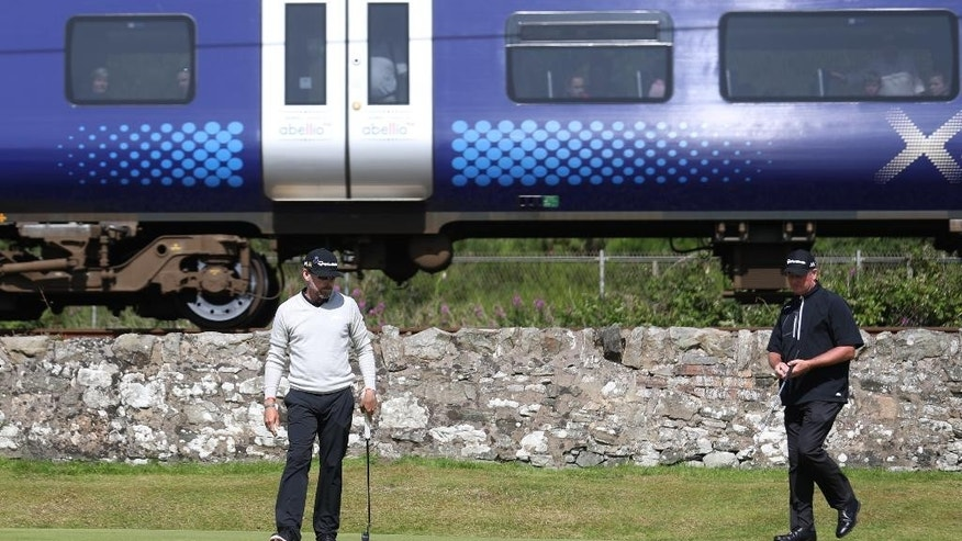 Justin Leonard of the US, left and playing partner Todd Hamilton of the US look at their putts as a passenger train passes by the 12th green during the first round of the British Open Golf Championship at the Royal Troon Golf Club in Troon, Scotland, Thursday, July 14, 2016. (AP Photo/Peter Morrison)