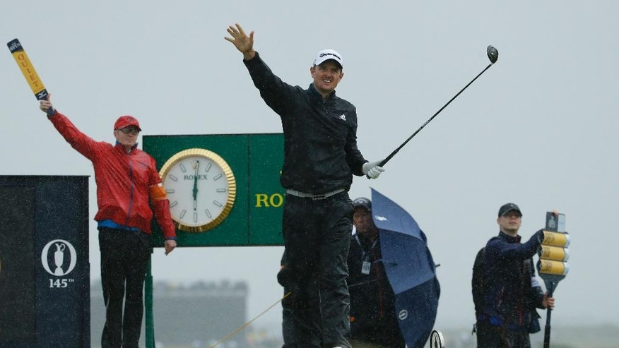 Justin Rose of England gestures after he tees off on the 15th tee in heavy rain during the second round of the British Open Golf Championship at the Royal Troon Golf Club in Troon, Scotland, Friday, July 15, 2016. (AP Photo/Matt Dunham)