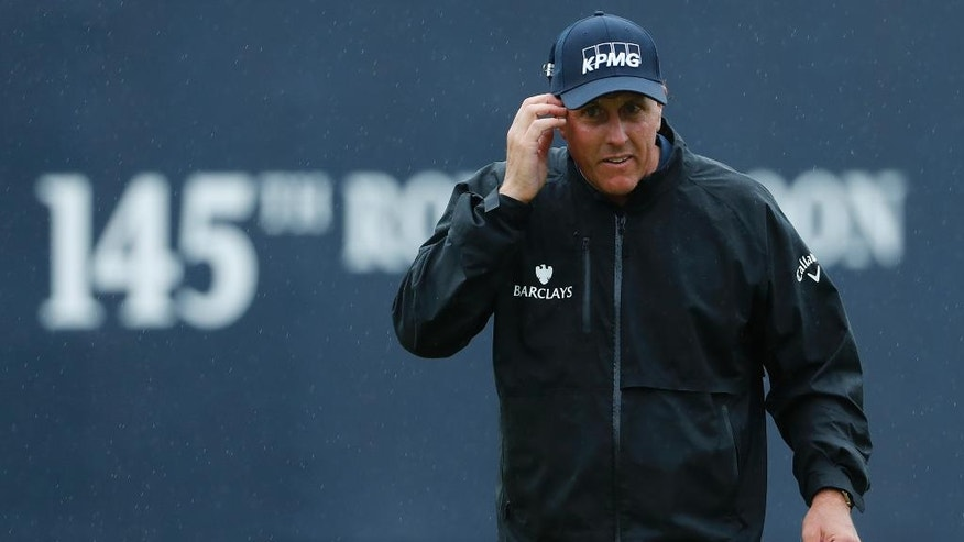 Phil Mickelson of the United States walks off the 18th green holding his score card after completing his second round of the British Open Golf Championships at the Royal Troon Golf Club in Troon, Scotland, Friday, July 15, 2016. (AP Photo/Ben Curtis)