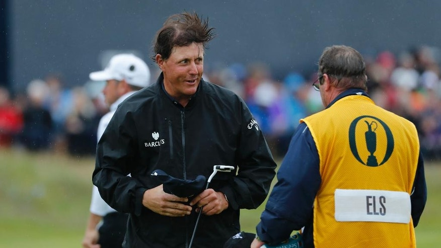 Phil Mickelson of the United States shakes hands with Ricci Roberts the caddie for Ernie Els on the 18th green, after completing his second round of the British Open Golf Championships at the Royal Troon Golf Club in Troon, Scotland, Friday, July 15, 2016. (AP Photo/Ben Curtis)