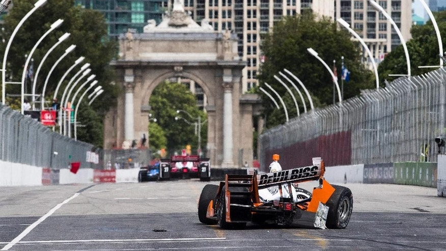 Drivers pass Team Penske driver Juan Pablo Montoya, of Colombia, after he crashed his car into a wall during practice sessions at the Honda Toronto Indy in Toronto, Friday, July 15, 2016. (Mark Blinch/The Canadian Press via AP)