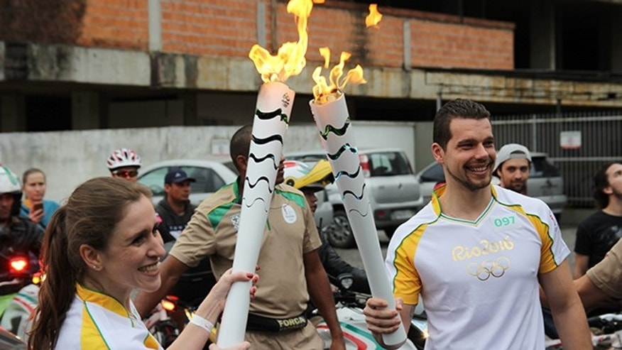 Former Olympic swimmer Eduardo Fischer (right) gets his relay torch lit for his leg of the Olympic relay in Joinville, Brazil. (Photo: Carolina Torres/Fox News Latino)