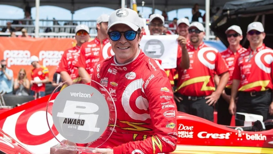 New Zealand's Scott Dixon holds his trophy after winning the pole position during qualifying for the IndyCar auto race in Toronto on Saturday, July 16, 2016. (Chris Young/The Canadian Press via AP)