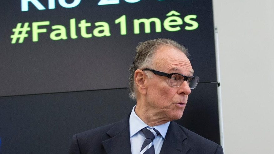 "FILE.- In this July 5, 2016 file photo Carlos Arthur Nuzman, president of the Rio 2016 Organizing Committee, stands in front of a sign promoting the Portuguese hashtag ""In one month,"" during the inauguration of the Olympic City Museum in Rio de Janeiro, Brazil. The world's top male golfers are skipping the Rio de Janeiro Olympics. Nuzman said on Saturday July 16, 2016 that golfers ""tried to blame Zika, but the media have shown that they are not coming because there's no prize money.""(AP Photo/Silvia Izquierdo, File)"
