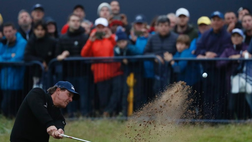 Phil Mickelson of the United States plays from a bunker on the 18th green during the third round of the British Open Golf Championship at the Royal Troon Golf Club in Troon, Scotland, Saturday, July 16, 2016.(AP Photo/Ben Curtis)
