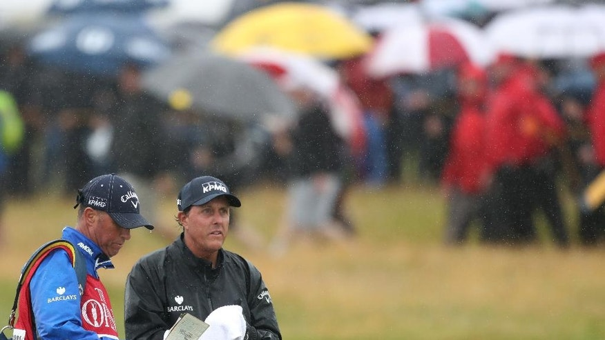 Phil Mickelson of the United States wipes his club as caddie Jim Mckay looks at his notebook as he waits to play from the 16th fairway during the second round of the British Open Golf Championships at the Royal Troon Golf Club in Troon, Scotland, Friday, July 15, 2016. (AP Photo/Peter Morrison)
