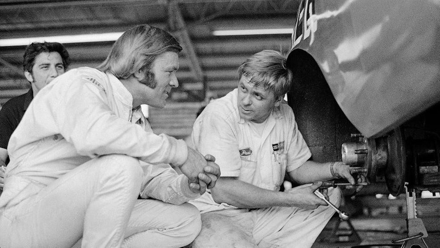 FILE - In this Aug. 1 1970, file photo, Fred Lorenzen, left, of Elmhurst, Ill., confers with a member of his pit crew, Paul Norris, of Charlotte, N.C., after winning the pole position for the Dixie 500 stock car race in Atlanta, Ga. He was one of NASCAR's first superstars, but  Lorenzen's memories of his Hall of Fame career have dimmed as he battles dementia. Now, Lorenzen has pledged his brain to the Concussion Legacy Foundation. He joins Dale Earnhardt Jr. as the only NASCAR drivers to make the pledge.  AP Photo/LG, File)
