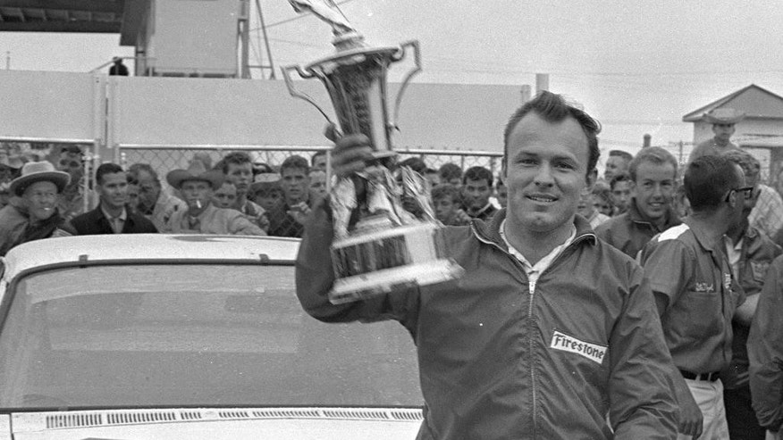 FILE - In this Feb. 14, 1965, file photo, Fred Lorenzen, of Elmhurst, Ill., gives a victory wave after winning the Daytona 500 mile stock car auto race which was halted by rain at the end of 133 laps, in Daytona Beach, Fla. He was one of NASCAR's first superstars, but  Lorenzen's memories of his Hall of Fame career have dimmed as he battles dementia. Now, Lorenzen has pledged his brain to the Concussion Legacy Foundation. He joins Dale Earnhardt Jr. as the only NASCAR drivers to make the pledge. (AP Photo/File)
