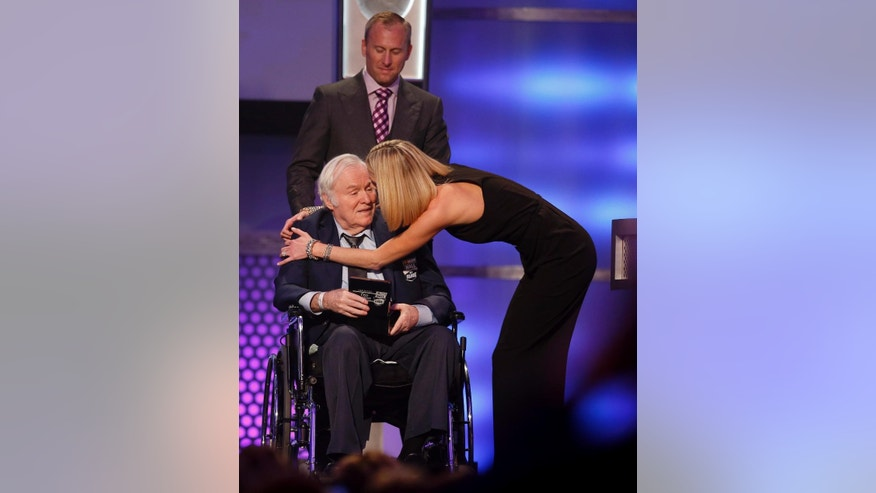 FILE - In this Jan. 30, 2015, file photo, Fred Lorenzen is embraced by his daughter Amanda as son Chris looks on as he is inducted into the NASCAR Hall of Fame in Charlotte, N.C. He was one of NASCAR's first superstars, but  Lorenzen's memories of his Hall of Fame career have dimmed as he battles dementia. Now, Lorenzen has pledged his brain to the Concussion Legacy Foundation. He joins Dale Earnhardt Jr. as the only NASCAR drivers to make the pledge. (AP Photo/Nell Redmond, File)