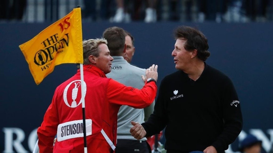 Phil Mickelson of the United States, right, shakes hands with the Gareth Lord, caddie of Henrik Stenson of Sweden, on the 18th green after he completed his third round of the British Open Golf Championship at the Royal Troon Golf Club in Troon, Scotland, Saturday, July 16, 2016. (AP Photo/Ben Curtis)