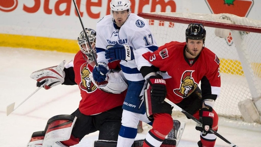 FILE - In this March 20, 2014, file photo, Tampa Bay Lightning center Alex Killorn, center, squeezes between Ottawa Senators goalie Robin Lehner and defenseman Marc Methot during the first period of an NHL hockey game in Ottawa. The Lightning avoided arbitration with Killorn, signing the forward to a $31.15 million, seven-year contract. (AP Photo/The Canadian Press, Adrian Wyld, File)