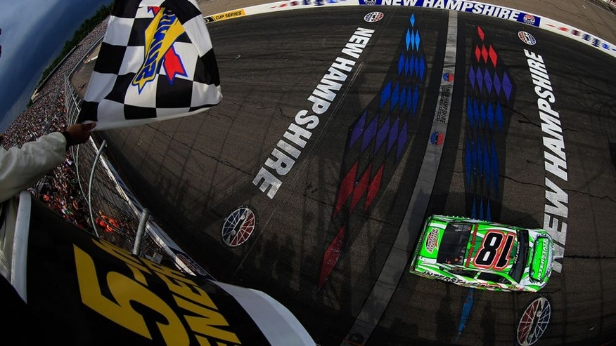 LOUDON, NH - JULY 19: Kyle Busch, driver of the #18 Interstate Batteries Toyota, takes the checkered flag to win the NASCAR Sprint Cup Series 5-Hour ENERGY 301 at New Hampshire Motor Speedway on July 19, 2015 in Loudon, New Hampshire. (Photo by Chris Trotman/NASCAR via Getty Images)