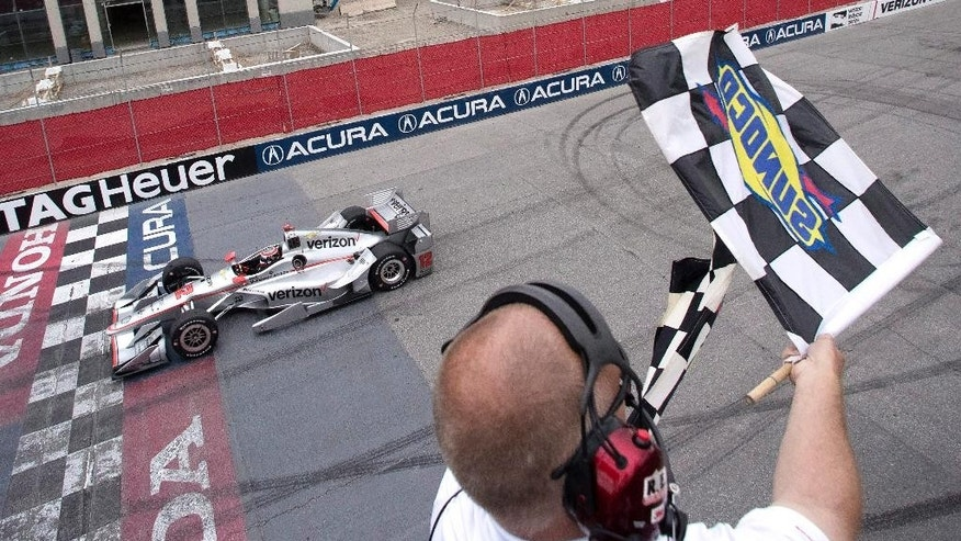 Will Power, of Australia, takes the checkered flag as he crosses the finish line to win the IndyCar auto race in Toronto on Sunday, July 17, 2016. (Mark Blinch /The Canadian Press via AP)