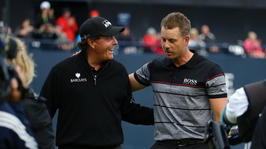 Phil Mickelson of the United States, left congratulates Henrik Stenson of Sweden for winning the British Open Golf Championships at the Royal Troon Golf Club in Troon, Scotland, Sunday, July 17, 2016. (AP Photo/Matt Dunham)