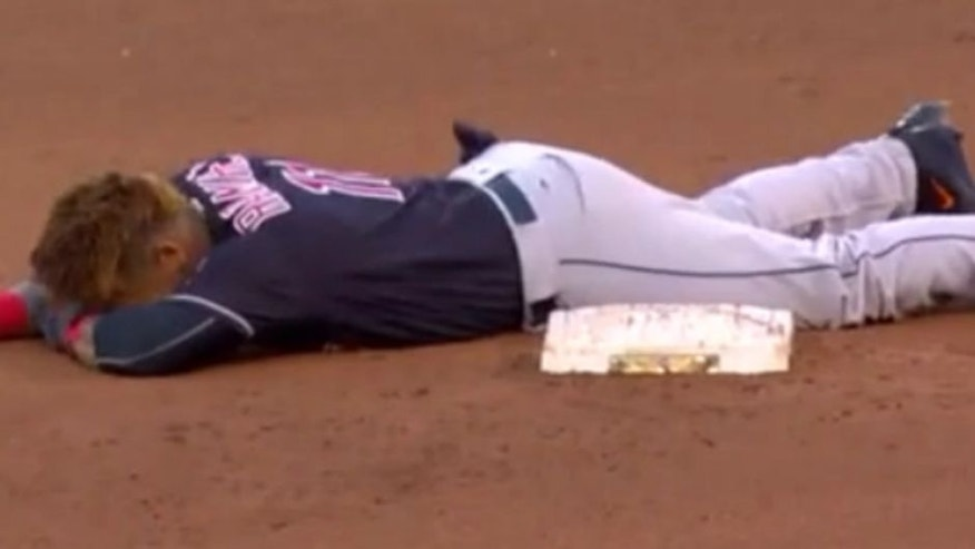 The Indians' Jose Ramirez slides face-first into second base.