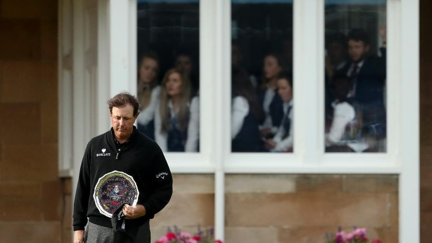 Phil Mickelson of the United States looks down as he holds the silver plate, for being runner up in the British Open Golf Championships at the Royal Troon Golf Club in Troon, Scotland, Sunday, July 17, 2016. Henrik Stenson the Championship. (AP Photo/Peter Morrison)