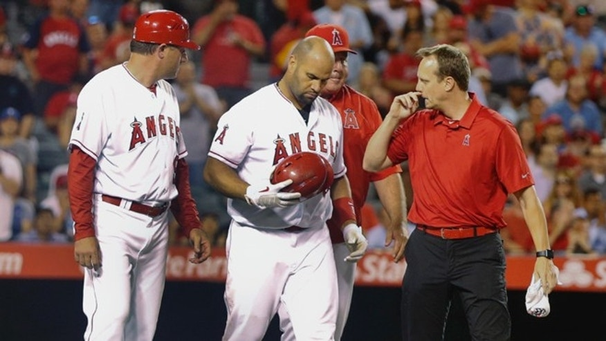 Los Angeles Angels' Albert Pujols is examined after being hit in the head by a pitch while batting in the seventh inning against the Texas Rangers in a baseball game Tuesday, July 19, 2016, in Anaheim, Calif. Pujols had hit two three run homers against the Rangers earlier in the game. (AP Photo/Lenny Ignelzi)