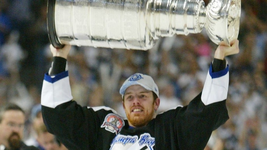 TAMPA, FL - JUNE 7: Brad Richards #19 of the Tampa Bay Lightning holds the Stanley Cup above his head after the victory over the Calgary Flames in Game seven of the NHL Stanley Cup Finals on June 7, 2004 at the St. Pete Times Forum in Tampa, Florida. The Lightning defeated the Flames 2-1. (Photo by Elsa/Getty Images)