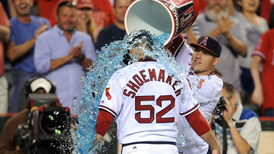 July 16, 2016; Anaheim, CA, USA; Los Angeles Angels center fielder Mike Trout (27) pours sport drink on starting pitcher Matt Shoemaker (52) in celebration of his 1-0 complete game victory against the Chicago White Sox at Angel Stadium of Anaheim. Mandatory Credit: Gary A. Vasquez-USA TODAY Sports