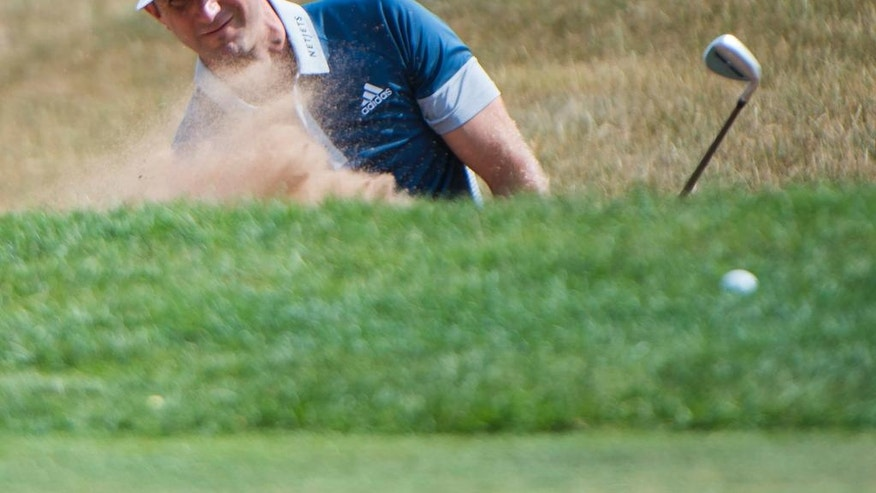 United States' Dustin Johnson blasts out of the bunker on the ninth hole at the 2016 Canadian Open in Oakville, Ontario, on Thursday, July 21, 2016. (Nathan Denette/The Canadian Press via AP)