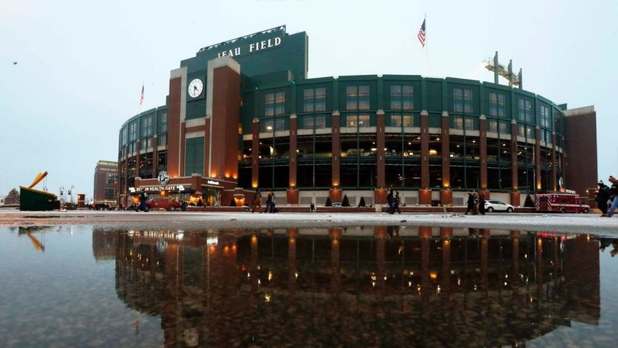 Lambeau Field is seen reflected in a puddle of water before the Packers-Falcons game in Green Bay, Wis.