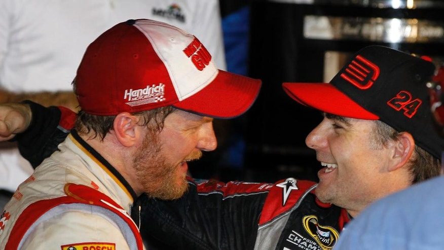 FILE - In this Feb. 23, 2014, file photo, Dale Earnhardt Jr., left, celebrates in Victory Lane with teammate Jeff Gordon, right, after winning the NASCAR Daytona 500 Sprint Cup series auto race at Daytona International Speedway in Daytona Beach, Fla. Gordon will get one more shot to win in Indianapolis this weekend when he replaces Earnhardt Jr. in the No. 88 car.  On Wednesday, July 20, 2016, Hendrick Motorsports announced that Earnhardt would miss the next two weeks as he continues to battle balance issues and nausea.  (AP Photo/Terry Renna, File)
