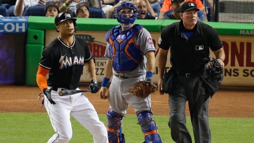 Miami Marlins' Giancarlo Stanton, left, watches his two-run home run in the third inning in front of New York Mets catcher Travis d'Arnaud during a baseball game in Miami, Saturday, July 23, 2016. (AP Photo/Joe Skipper)
