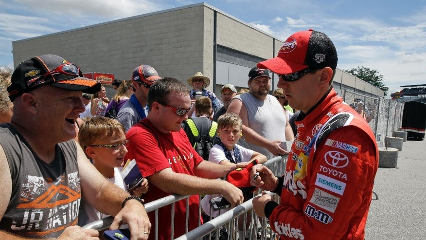 Sprint Cup Series driver Kyle Busch (18) signs autographs for fans following a practice session for the Brickyard 400 NASCAR auto race at the Indianapolis Motor Speedway in Indianapolis, Friday, July 22, 2016. (AP Photo/Michael Conroy)