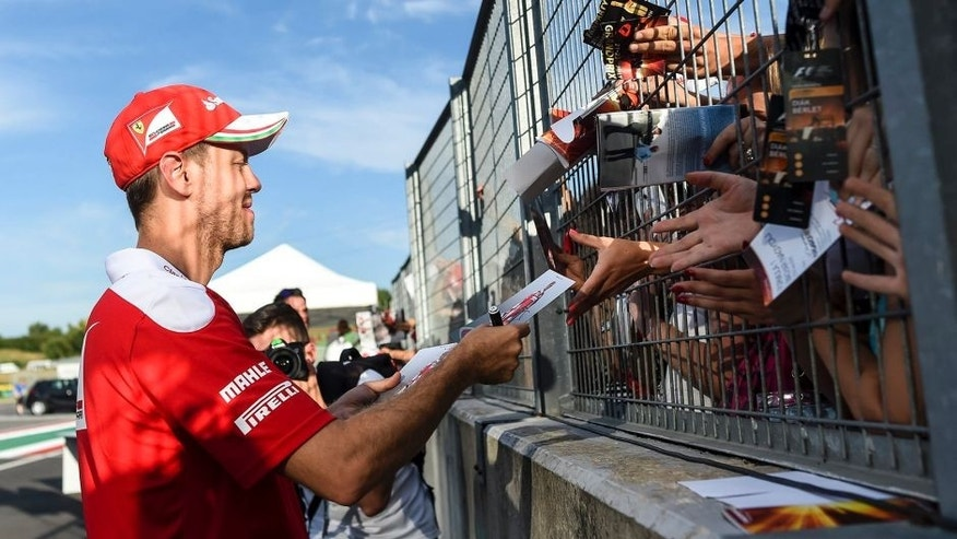 Ferrari driver Sebastian Vettel of Germany signs autographs at the Hungaroring racetrack, in Budapest, Hungary, Thursday, July 21, 2016. The Hungarian Formula One Grand Prix will be held on Sunday July, 24. (Janos Marjai/MTI via AP)