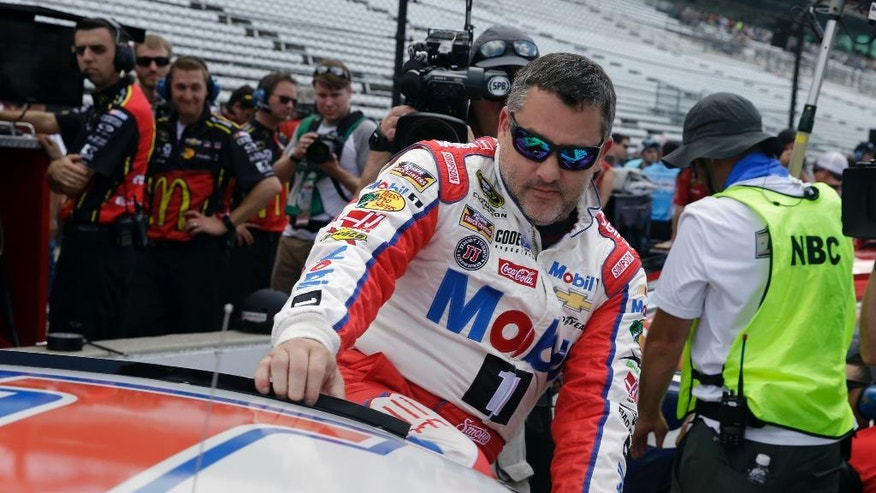 Sprint Cup Series driver Tony Stewart (14) climbs into his car before qualifications for the Brickyard 400 NASCAR auto race at Indianapolis Motor Speedway in Indianapolis, Saturday, July 23, 2016. (AP Photo/Michael Conroy)