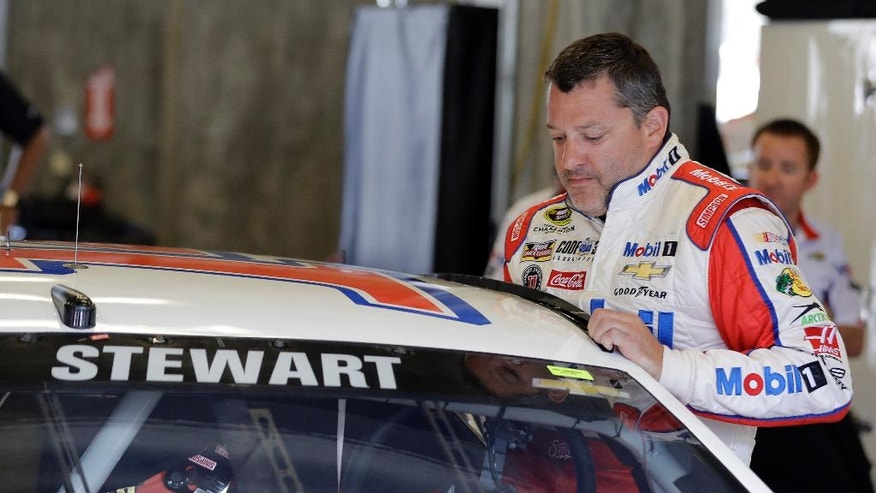 Sprint Cup Series driver Tony Stewart (14) climbs into the car during practice for the Brickyard 400 NASCAR auto race at the Indianapolis Motor Speedway in Indianapolis, Friday, July 22, 2016. (AP Photo/Darron Cummings)