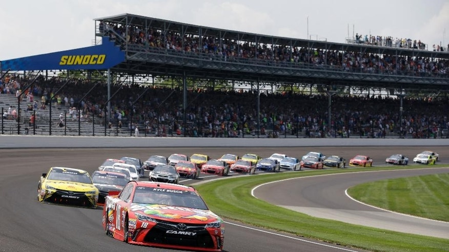 Kyle Busch (leads the field through the first turn on the start of the Brickyard 400 NASCAR auto race at Indianapolis Motor Speedway in Indianapolis, Sunday, July 24, 2016. (AP Photo/Michael Conroy)