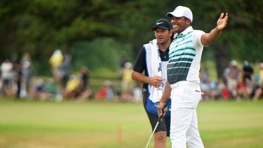 Jhonattan Vegas, right, of Venezuela, reacts on the 18th green during the final round at the Canadian Open golf tournament in Oakville, Ontario, Sunday, July 24, 2016. (Nathan Denette/The Canadian Press via AP)