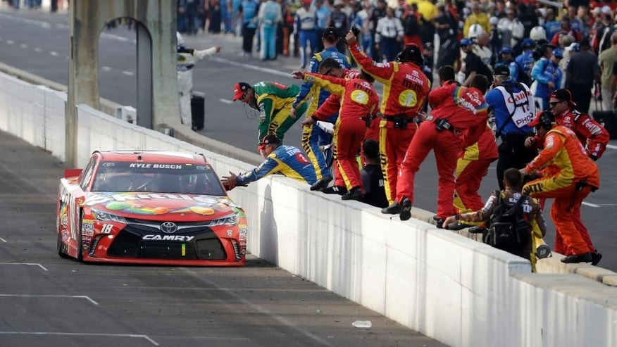 Kyle Busch celebrates with his crew after winning the Brickyard 400 NASCAR Sprint Cup auto race at Indianapolis Motor Speedway in Indianapolis, Sunday, July 24, 2016. (AP Photo/Darron Cummings)
