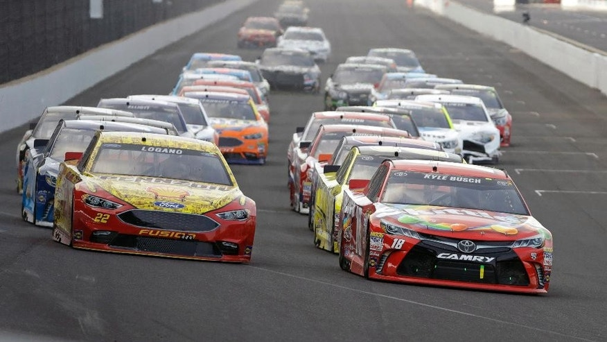 Kyle Busch (18) leads Joey Logano (22) into the first turn on the final restart of the Brickyard 400 NASCAR auto race at Indianapolis Motor Speedway in Indianapolis, Sunday, July 24, 2016. (AP Photo/Darron Cummings)