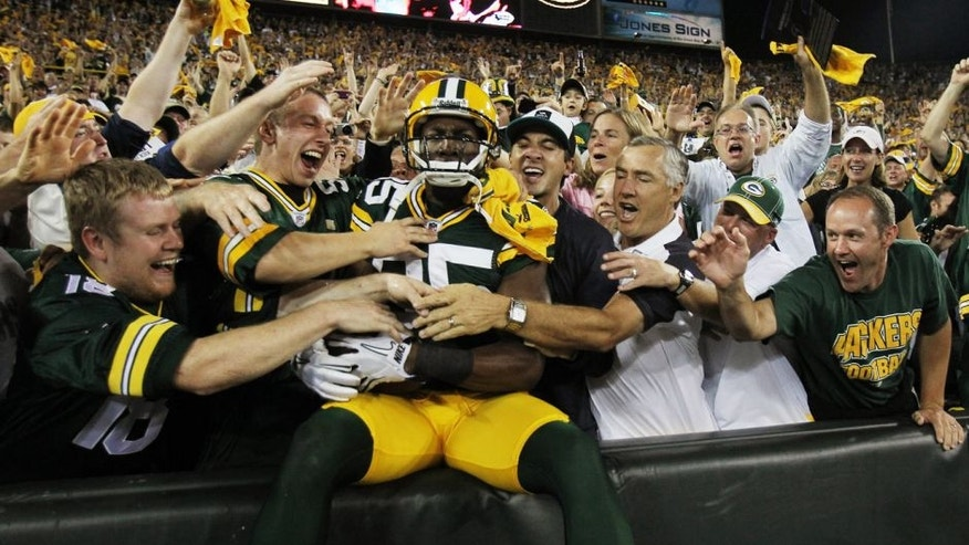 GREEN BAY, WI - SEPTEMBER 08: Greg Jennings #85 of the Green Bay Packers is mobbed by fans after leaping into the stands following a touchdown catch against the New Orleans Saints during the NFL opening season game at Lambeau Field on September 8, 2011 in Green Bay, Wisconsin. The Packers defeated the Saints 42-34. (Photo by Jonathan Daniel/Getty Images)