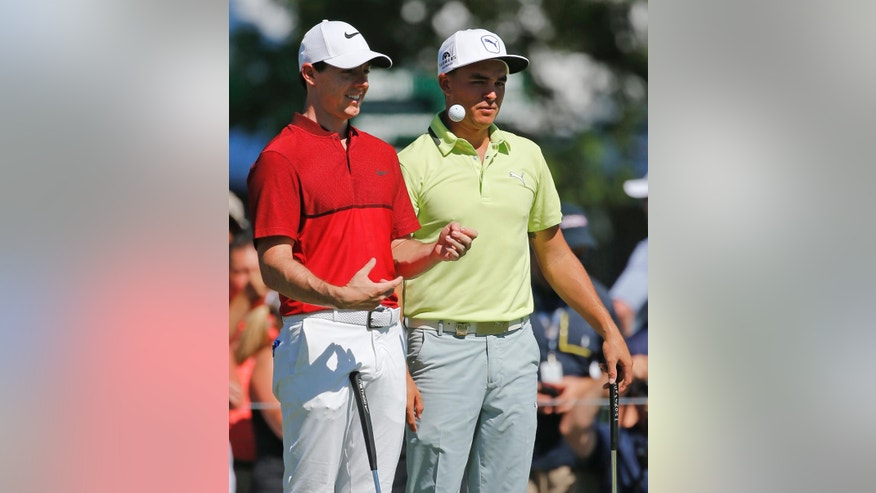 Rory McIlroy, left, talks with Rickie Fowler, right, as they wait on the fifth hole during a practice round for the PGA Championship golf tournament at Baltusrol Golf Club in Springfield, N.J., Tuesday, July 26, 2016. (AP Photo/Mike Groll)