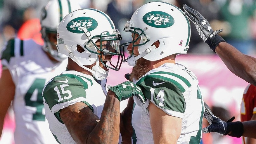 Oct 18, 2015; East Rutherford, NJ, USA; New York Jets quarterback Ryan Fitzpatrick (14) celebrates with wide receiver Brandon Marshall (15) after scoring a touchdown in the second half against the Washington Redskins at MetLife Stadium. The Jets won 34-20. Mandatory Credit: Vincent Carchietta-USA TODAY Sports