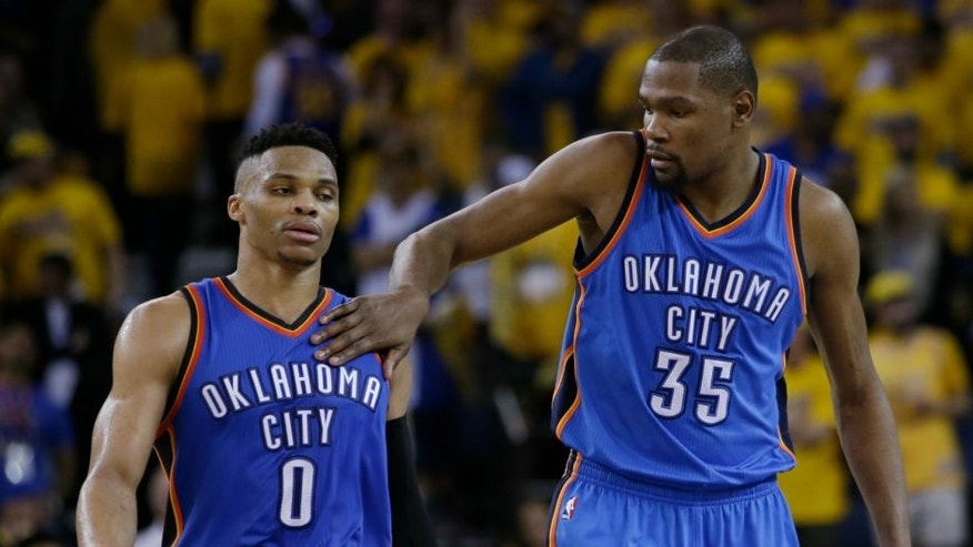 Oklahoma City Thunder's Kevin Durant (35) pats teammate Russell Westbrook (0) on the shoulder as they take a lead over the Golden State Warriors during the second half in Game 1 of the NBA basketball Western Conference finals Monday, May 16, 2016, in Oakland, Calif. Oklahoma City won 108-102. (AP Photo/Marcio Jose Sanchez)