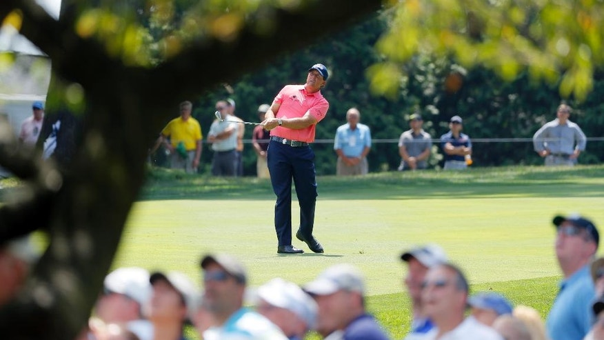 Phil Mickelson watches his approach shot on the third hole during the first round of the PGA Championship golf tournament at Baltusrol Golf Club in Springfield, N.J., Thursday, July 28, 2016. (AP Photo/Tony Gutierrez)